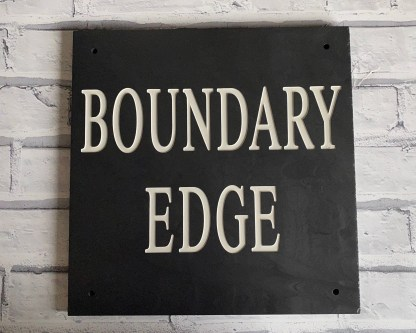 a piece of 30cm square welsh grey slate, engraved with a house name designed to be fixed to an oak frame