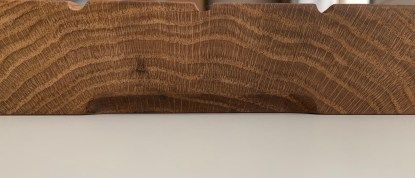 grooves on the underside of a solid oak bread board, designed to facilitate lifting