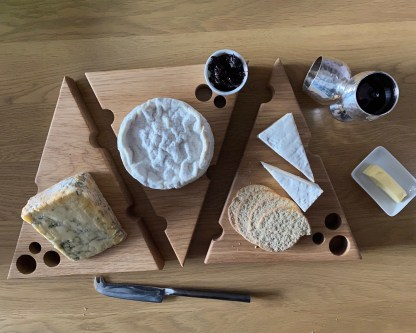 aerial view of a solid oak cheese board made in the shape of a wedge with holes along the edges and surface to make it look like a piece of cheese