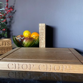 solid oak chopping board with cross grooves on the surface and chop chop engraved along the front edge. slate and oak handcrafted personalised oak gifts
