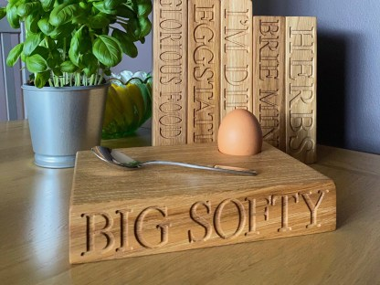 aerial shot of oak dippy egg board, complete with egg, and engraved with the text, big softy