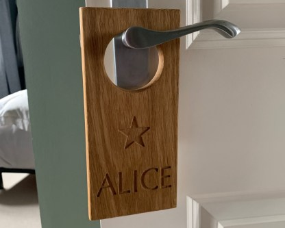 personalised door hanger. solid oak plaque engraved with a christian name and a star image, with a large hole designed to fit over a door handle denoting the name of the room or who it belongs to. slateandoak