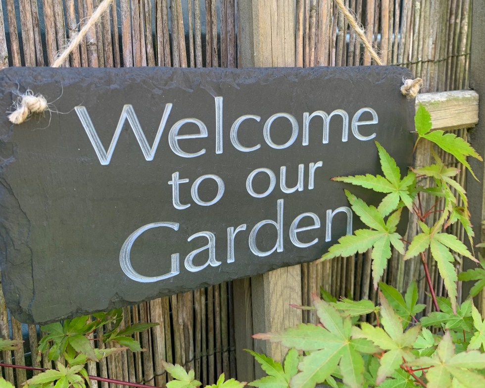 welsh grey slate garden sign engraved with welcome to our garden strung with natural jute rope
