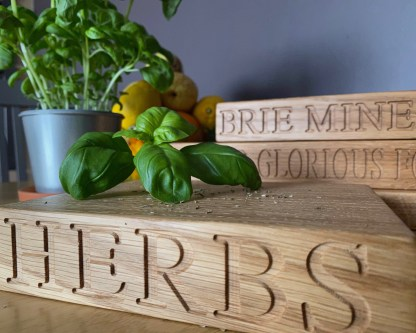 close up of a small oak chopping board which has the word herbs engraved along the front edge. the engraving is clearly visible as is the grain in the timber