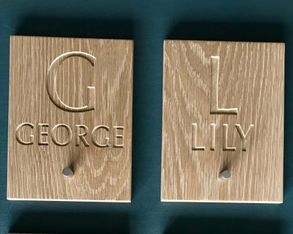 solid oak plaques engraved with an initial and a christian name and fitted with a small chrome knob designed for hanging up coats, robes or bags