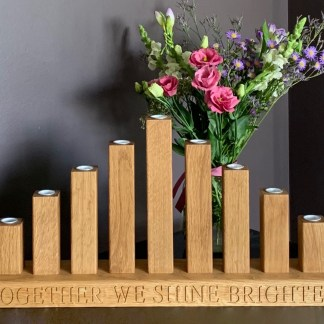 slateandoak solid oak candle bridge with 9 oak candle sticks in a cascading style fitted to a solid oak base which has together we shine brighter engraved along the front edge