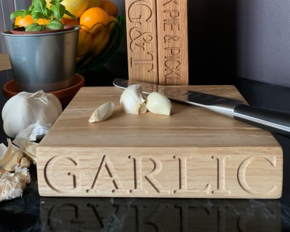 small solid oak chopping block engraved with garlic along one edge and onion along another edge