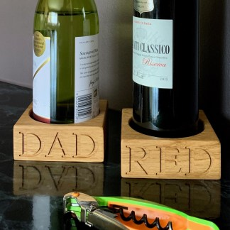 solid oak square block with a recess in the middle designed for a wine bottle, engraved along the front edge with dad or red