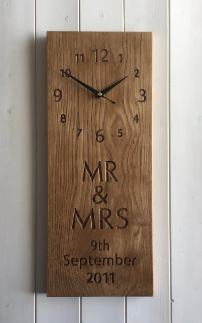 long thin solid oak wall clock engraved with a full face of numbers and personalised text in the bottom half