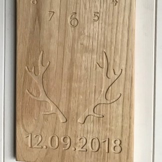 close up of a long thin solid oak wall clock with stag antlers and a date engraved in the bottom half