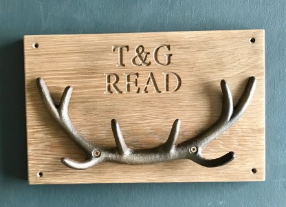 solid oak plaque engraved with a name and a date and fitted with cast iron stag antlers for use as a coat or key rack