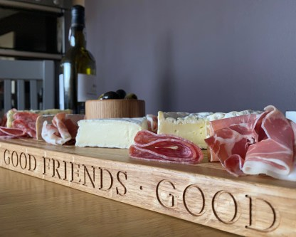 long thin solid oak serving board engraved along the front edge with good food, good friends, good times. slate and oak personalised oak gifts handcrafted in solid oak