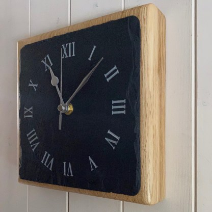 side view of a square piece of welsh grey slate engraved with a roman numerals style clock face mounted on a thick oak block for wall mounting or freestanding