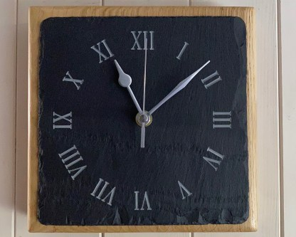 a square piece of welsh grey slate engraved with a roman numerals style clock face mounted on a thick oak block for wall mounting or freestanding