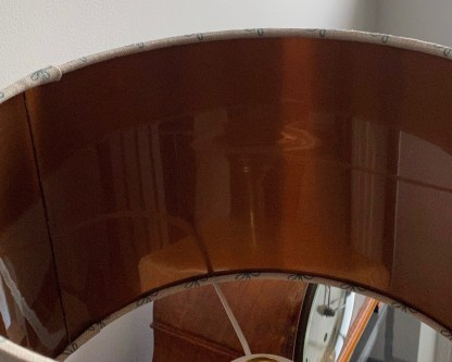 close up view of the brushed copper lining on a drum lampshade made with a natural linen fabric