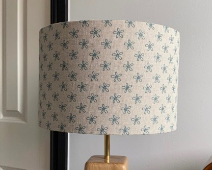 drum lampshade in natural linen with teal blue daisy print, on a solid oak lamp base with brass fittings
