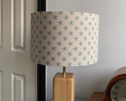 30cm natural linen drum lampshade with a teal blue daisy design, on a solid oak lamp base with brass upriser
