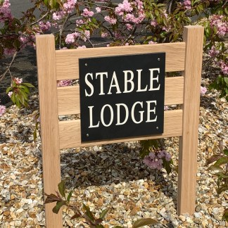 30cm square honed welsh grey slate engraved with a house name, fitted to a solid oak frame designed for fixing into the ground. The frame has 2 posts and 3 cross rails which support the piece of slate