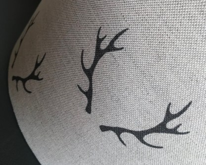 close up view of charcoal coloured stag antlers printed on natural linen fabric