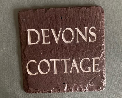 square piece of handcut welsh heather slate engraved with devons cottage in upper case characters across two lines of text