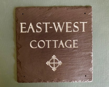 square piece of handcut welsh heather slate engraved with east west cottage across 2 lines with an image of a compass engraved at the bottom of the slate
