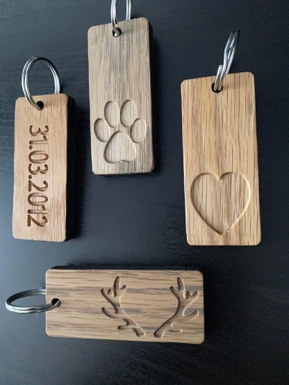solid oak keyrings finished with graphite coloured oil and engraved with a paw, an antler, a heart and a date