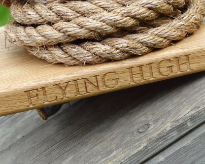 close up of the front edge of a solid oak monkey swing with flying high engraved. slateandoak
