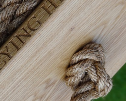 underneath of a solid oak monkey swing showing the knot in the manilla rope