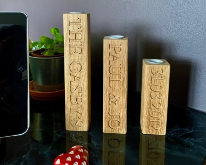 set of 3 solid oak personalised candle sticks each one engraved with names and dates. slateandoak