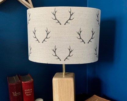 natural linen fabric digitally printed with a charcoal coloured pair of stag antlers arranged in a step repeat pattern. slateandoak