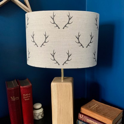 drum lampshade in natural linen fabric digitally printed with a pair of charcoal coloured stag antlers arranged in a step repeat pattern