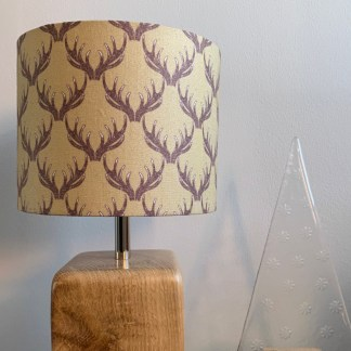 drum lampshade in khaki coloured cotton fabric printed with a blackberry coloured series of stag antlers