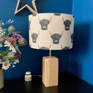 drum lampshade in natural linen fabric digitally printed with a black and white highland cow image in a stepped repeat pattern