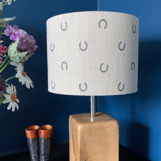 drum lampshade in natural linen fabric with a digital print of a single horseshoe in a step pattern