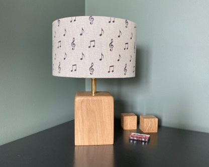 drum style lampshade made using natural linen fabric printed with a series of musical notes in a dark charcoal colour