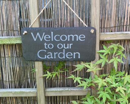 hand cut welsh grey slate engraved with welcome to our garden and hung with a length of natural jute rope