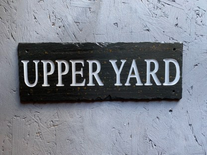 full view of engraved slate stable sign with the text upper yard.