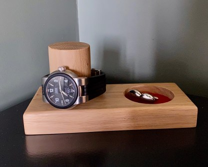 solid oak watch and cufflink tray complete with watch placed over the vertical post and cufflinks in the recessed tray