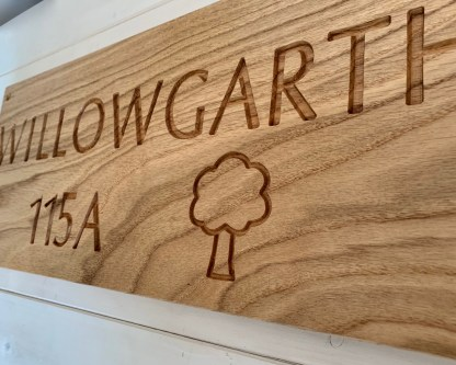 profile view of a oak house sign with the outline image of a tree