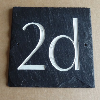 15cm square black slate engraved with 2d as a house sign. holes drilled either side in the slate to facilitate fixing to a wall