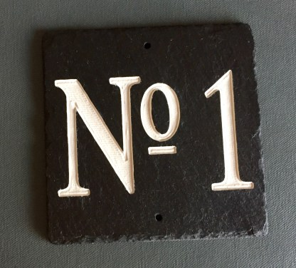 15cm piece of welsh grey slate engraved with house number No 1 then painted in off white and finished with a matt sealer