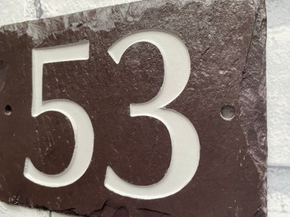 side view and close up of welsh heather slate house number, engraved with 53. slate has drill holes either side for fixing