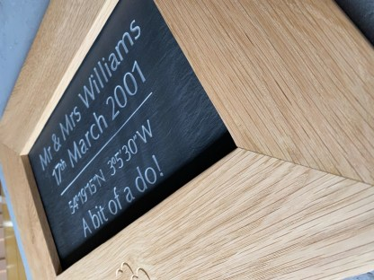 inset view of a solid oak frame with engraved slate insert.
