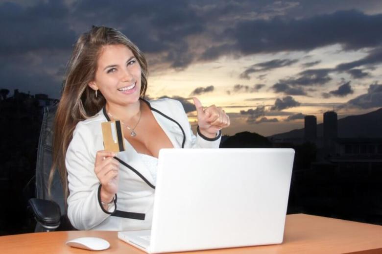 La ragazza in vestito che tiene una carta di credito e che fa un pollice in su firma mentre esamina un computer.