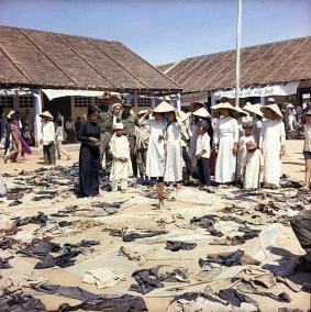 Major Gordon Brown, AATTV, and Vietnamese Women Stand Before Rotting Clothing