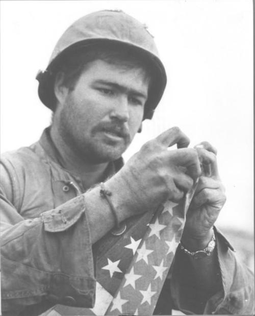 Marine Fashions the U.S. flag in Preparation to Hoist it Over the Citadel in the Imperial City - Remembering The Vietnam War