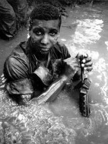 Soldier Cools Off in a Stream in the Mekong Delta Whilst Cleaning His Weapon