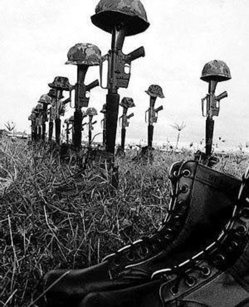 Soldiers Boots Helmets And Rifles Lined Up - Remembering The Vietnam War