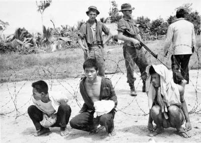 Suspected Viet Cong Sit Inside a Barbed Wire Enclosure Guarded by Member of 1RAR