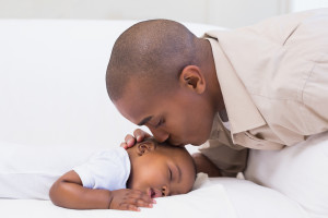Adorable baby boy sleeping while being watched by father at home